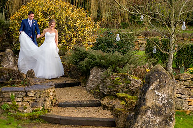 Groom helps Bride walk down garden path