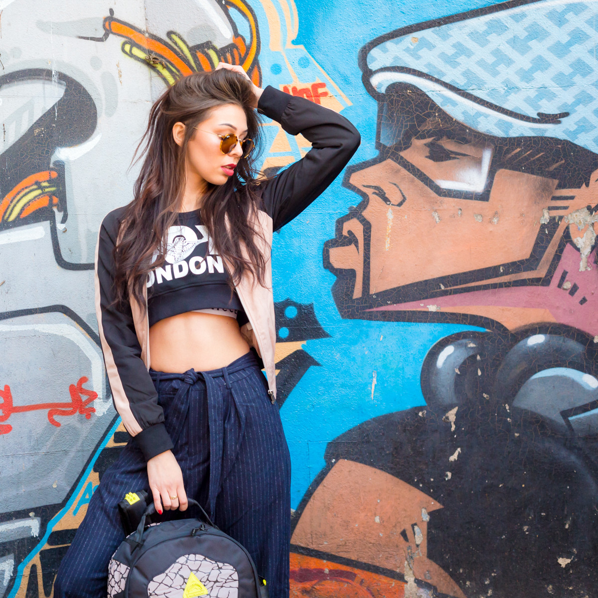 model posing in crop top next to graffiti