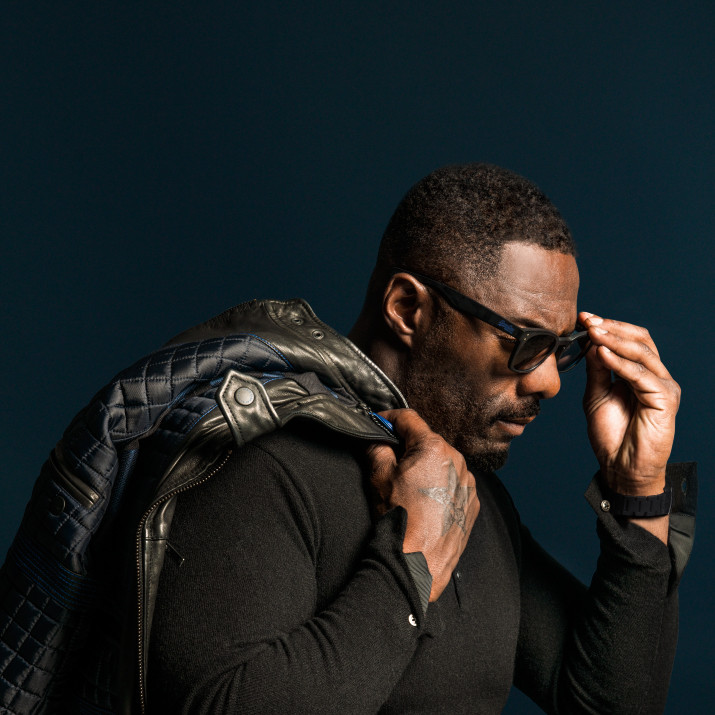 Idris Elba hollywood actor looking cool and holding a Superdry leather jacket