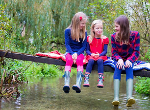 Sisters sat on a home made bridge over a stream in Hampshire