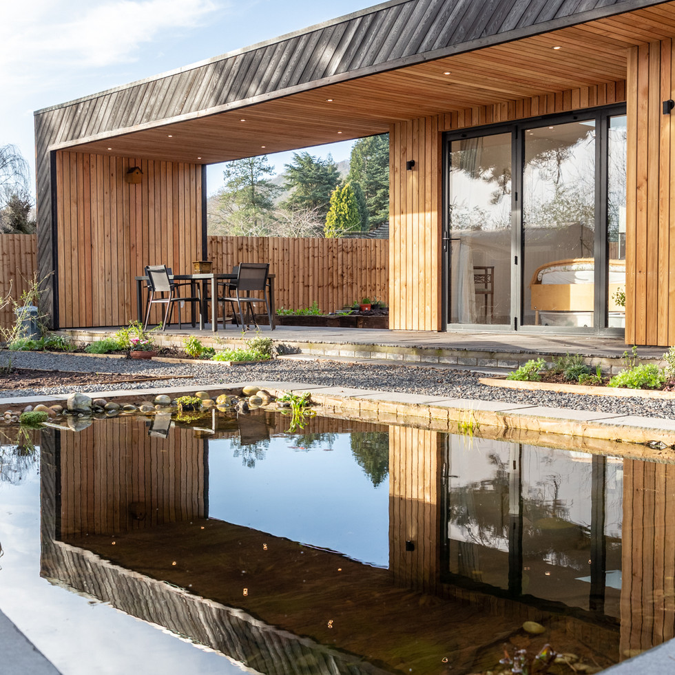 Modern timber clad home reflected in garden pond