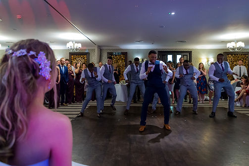bride watches her new husband and groomsmen dancing