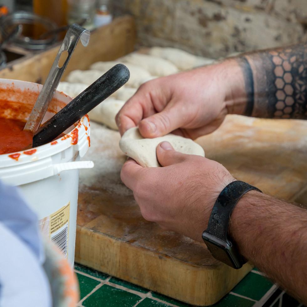 tattooed male kneeding pizza dough