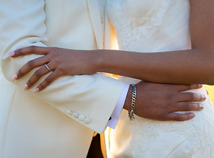 Groom in white suit embraces new wife
