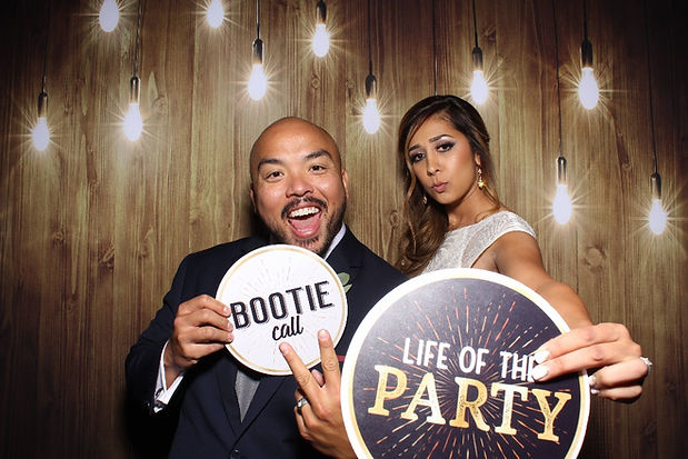 Couple Posing For Photo Booth Rental With A Rustic Wood Backdrop