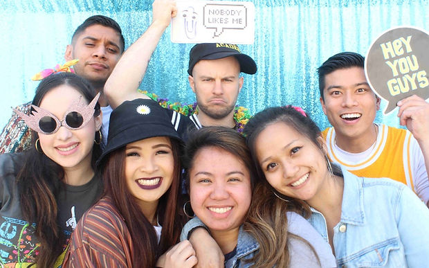College Students Posing For A College Event In Front Of Teal Photo Booth Backdrop