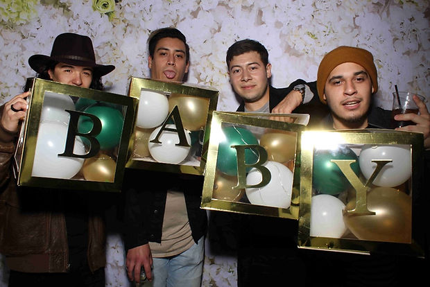 Group Of Friends Posing With Signs That Spell Baby For The Photo Booth Rental
