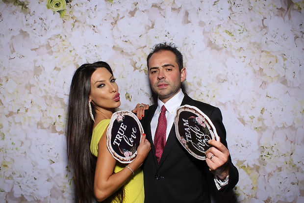 Couple Posing For Photo Booth At A Wedding With White Flower Backdrop