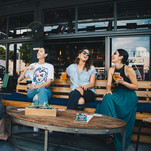 four-women-chatting-while-sitting-on-ben