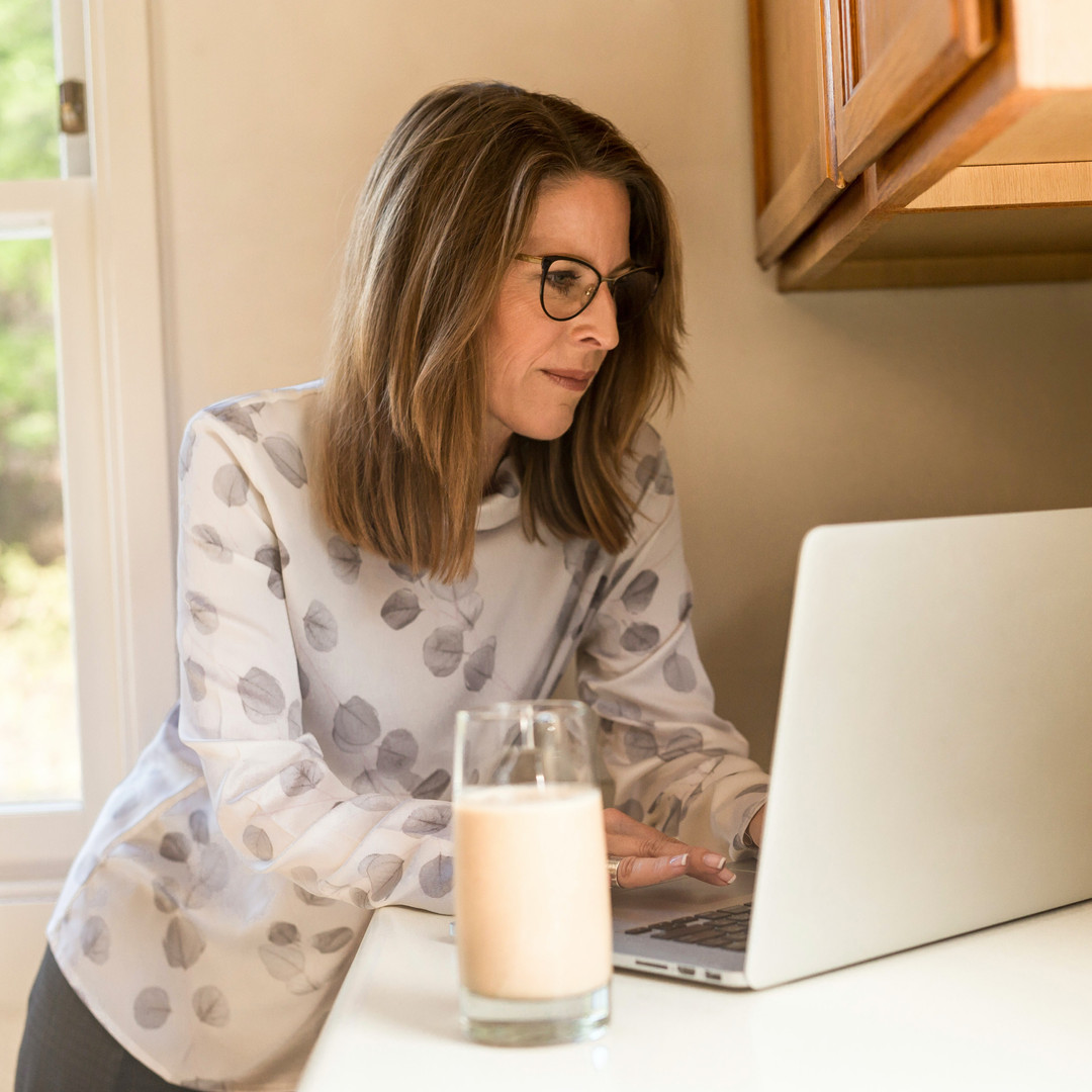 woman-using-gray-laptop-computer-in-kitc