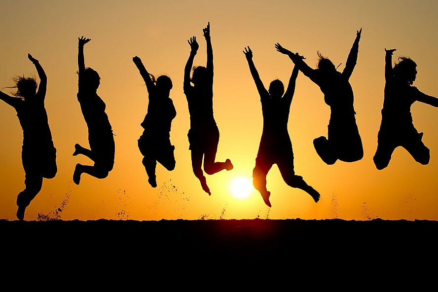 Seven people in silhouette leaping for joy