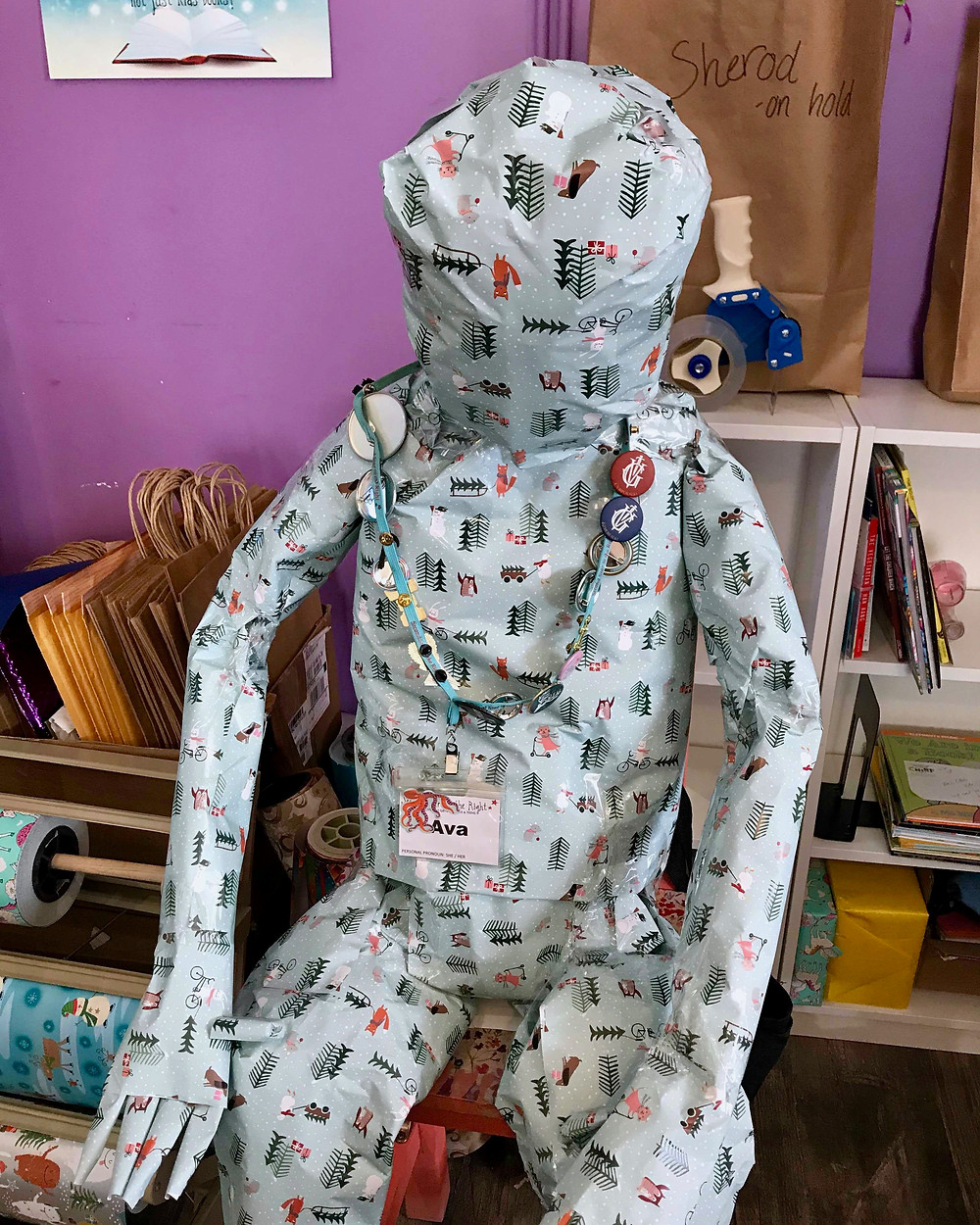 Holiday wrapping paper shaped to look like human sitting on stool in front of other wrapping materials and shopping bag. Lanyard with buttons is looped around its neck with nametag reading 'Ava.'