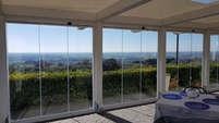 Vetrata frangivento tutto vetro per su portico in legno