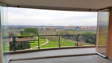 Vetrata scorrevole frangivento panoramica su balcone a Roma