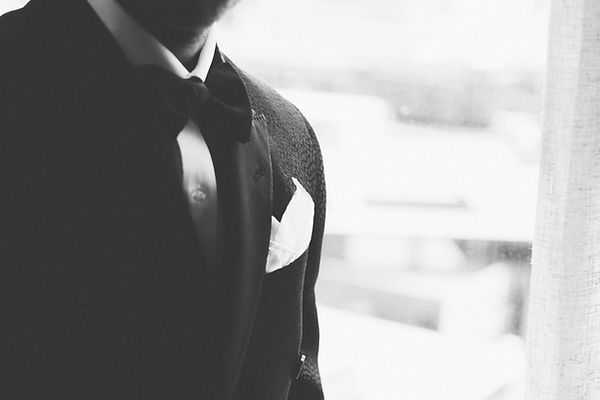 Groom in a black tuxedo suit with bowtie and pocket square