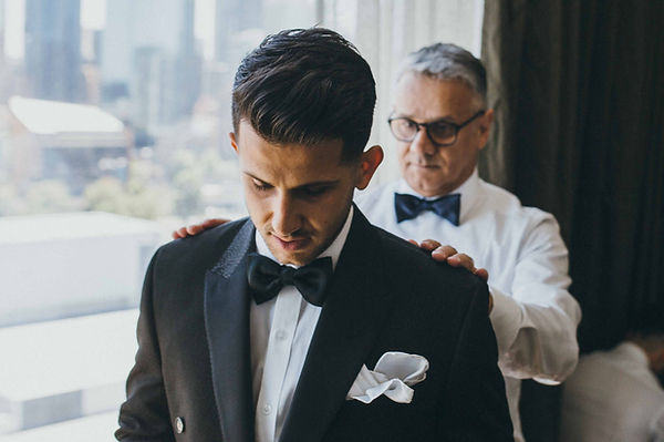 Groom in a tailored black suit with his personal tailor in glasses