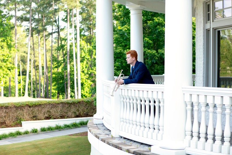 formal senior boy portrait, trumpet, balcony
