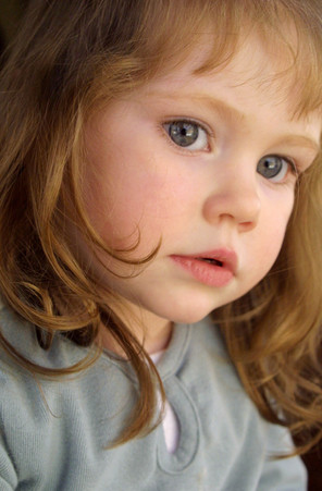 sweet, thoughtful toddler with big gray eyes portrait