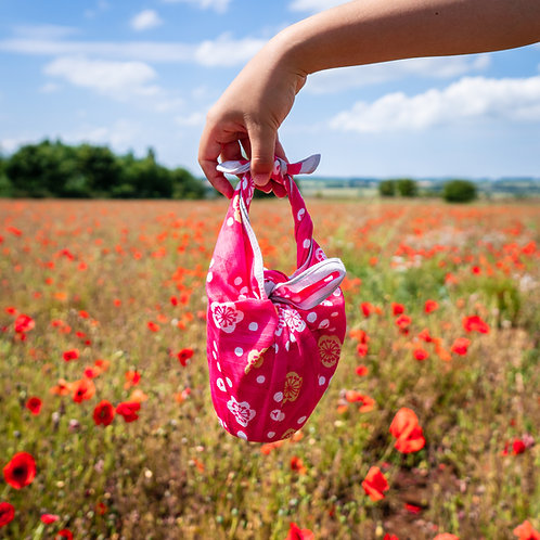 Japanese Apricot pink furoshiki gift wrapped present in a poppy field