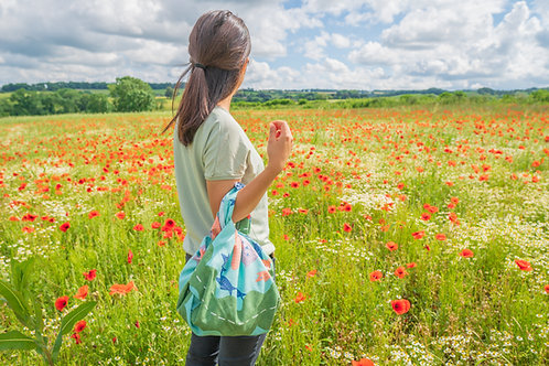 otter furoshiki bag being carried in a poppy field