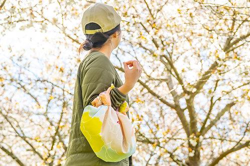 Organic furoshiki bag being carried in a garden