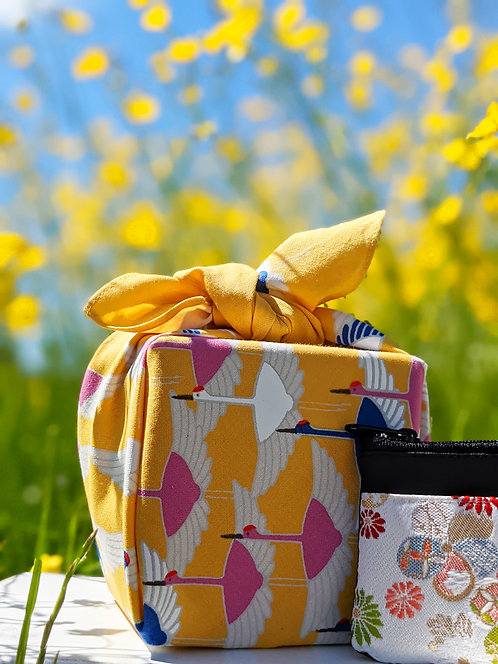 Crane Yellow furoshiki gift wrapping present in a wild flower meadow