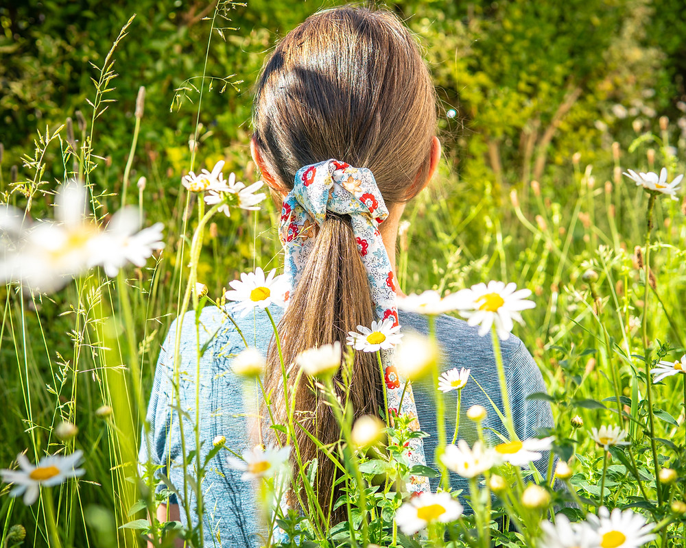 woman sitting in a meadow with a furoshiki hair tie