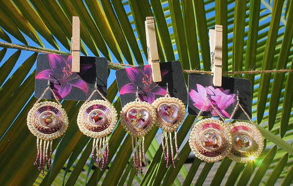 Beaded earrings hanging on a clothesline.