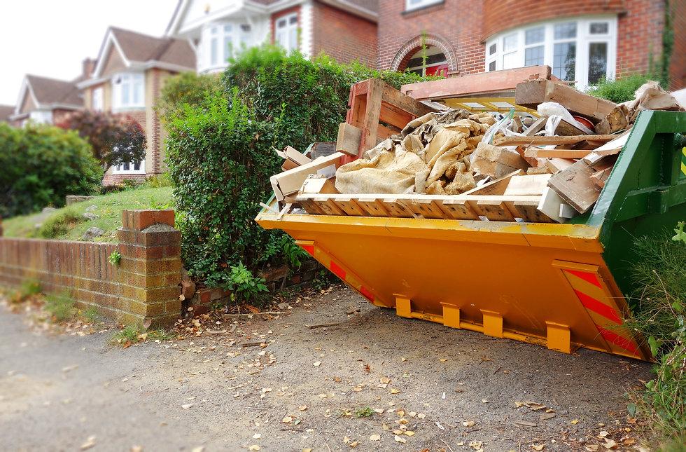 Yellow rubbish skip on driveway. Selecti