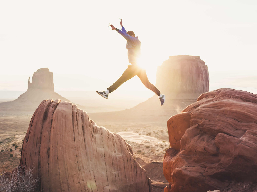 Blogish - The Productivity Club - Don't Give Up - Man Jumping Over Mountain