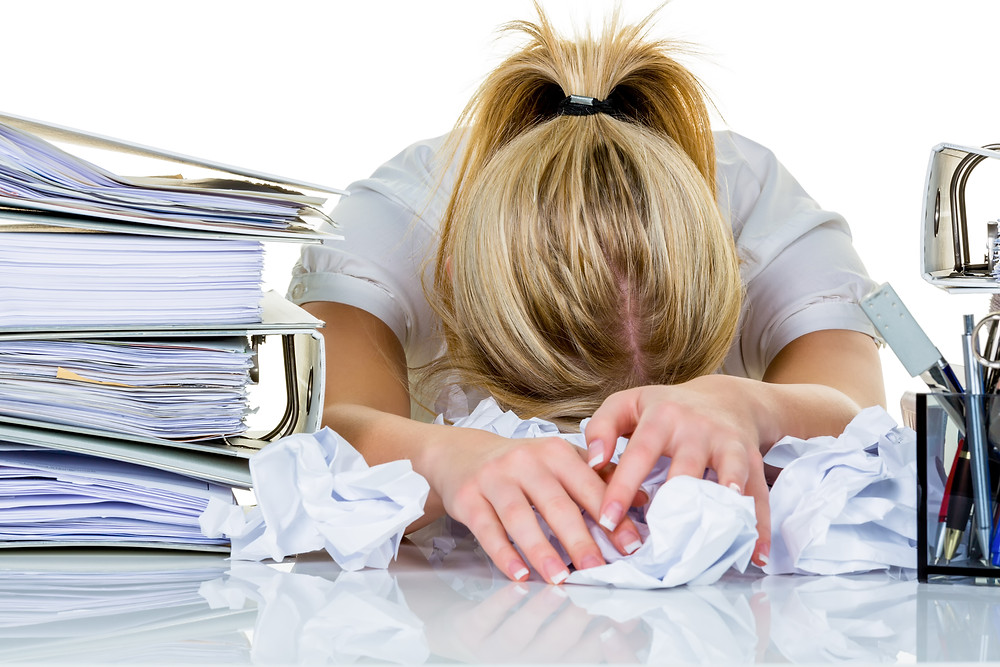 Woman slumped over heap of papers on desk