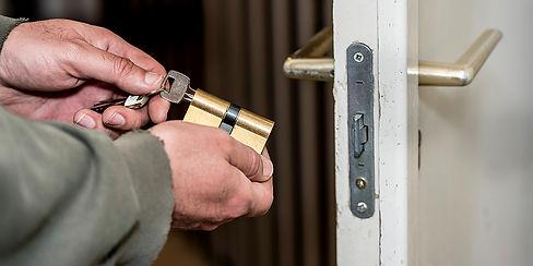 Male-handyman-worker-wood-door-lock-inst