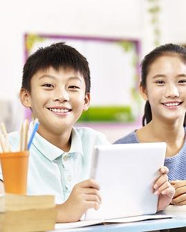 portrait of two happy asian primary scho