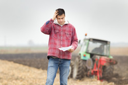 Worried young farmer standing on field a