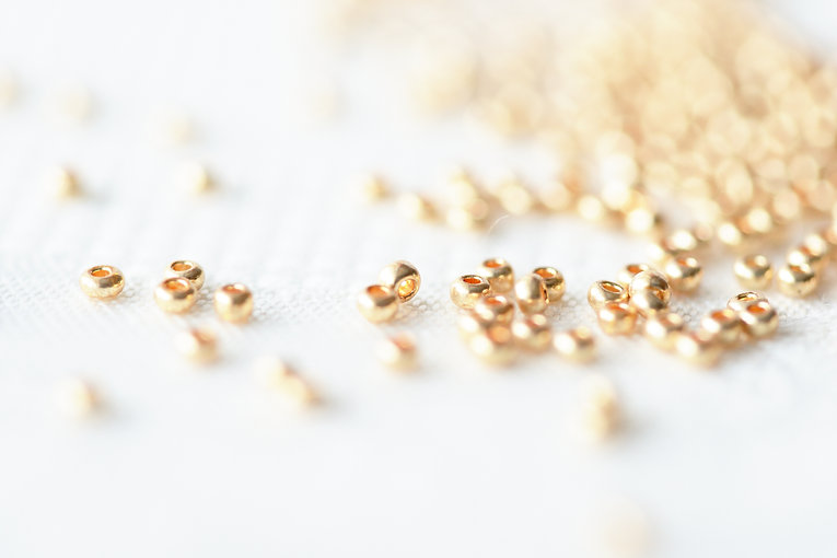 Golden seed beads scattered on textile b