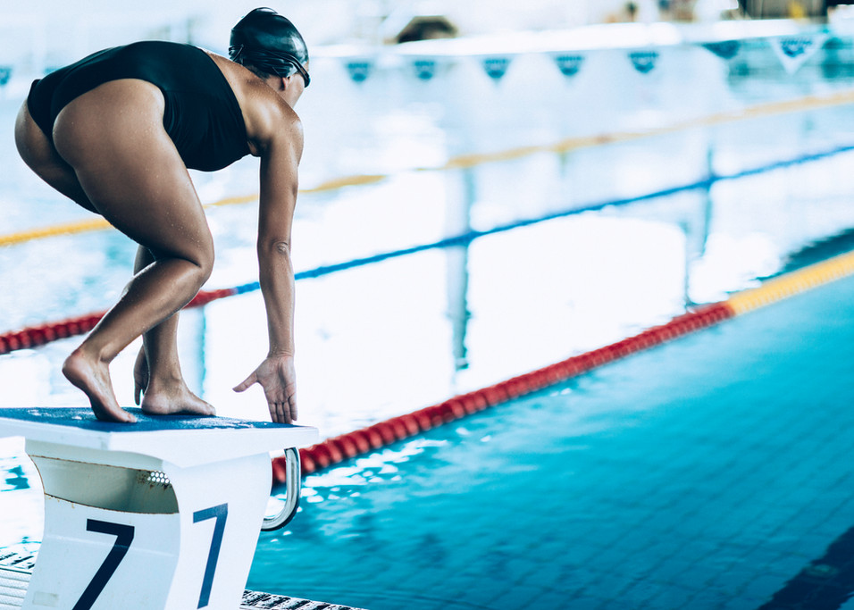 Girl about to dive in to the pool off a diving block
