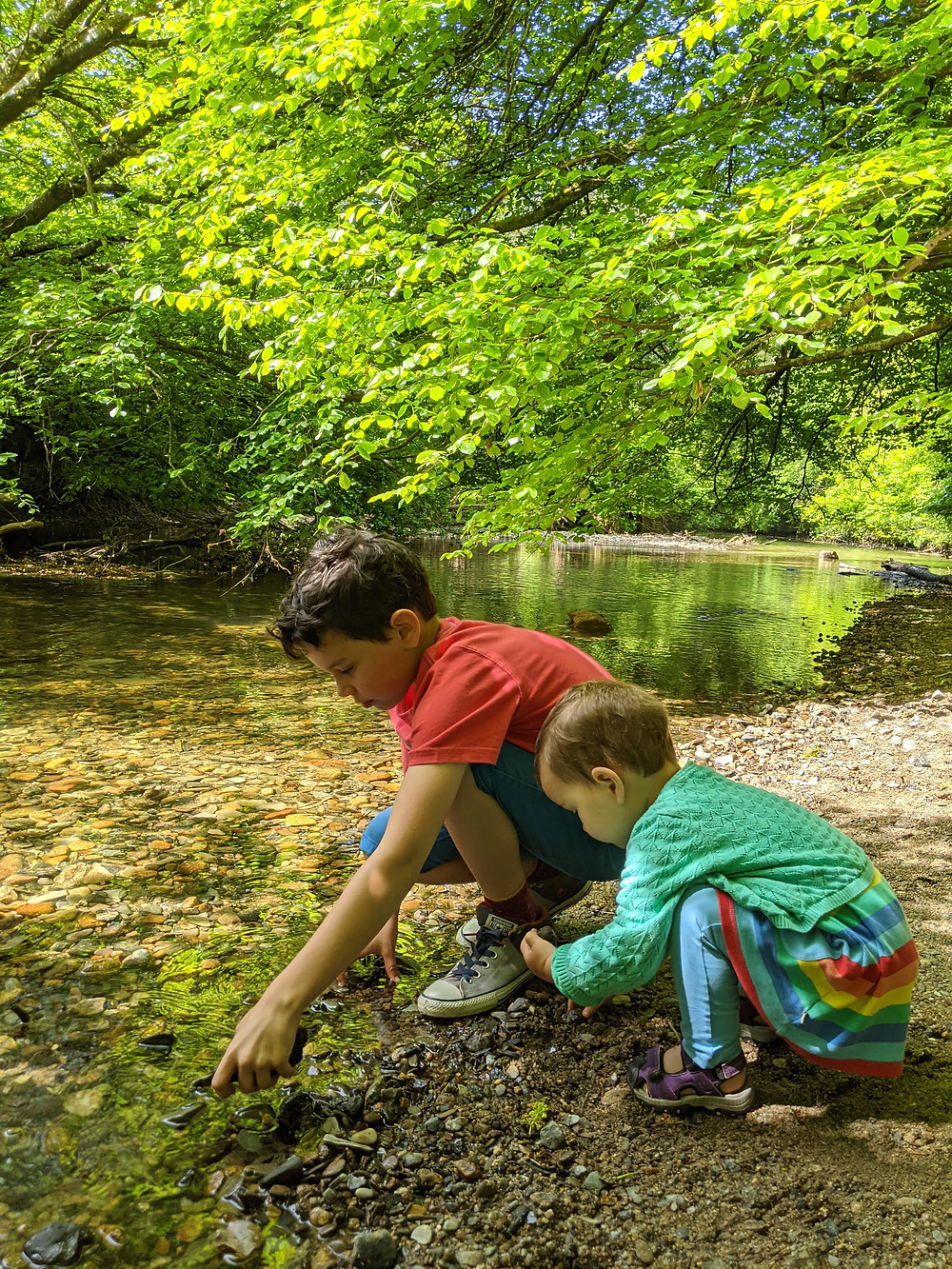 Happy in nature - Kids playing by a river in pre-loved clothing from Animal T-Shirt, Next shorts, Converse trainers, Frugi Organic rainbow tunic & leggings, Karrimor sandals & Marks and Spencers cardigan.