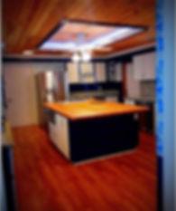 Kitchen -  butcher block island, French door fridge, dark blue walls, white cabinets, tongue and groove cedar and pine ceiling. Oak look laminate floor.