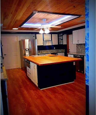 Kitchen -  butcher block island, French door fridge, dark blue walls, white cabinets, tongue and groove cedar and pine ceiling. Oak look laminate floor.