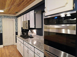 Partial kitchen view with gas stove, microwave, double convection ovens and quartz countertop.