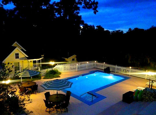 Evening view from 2nd floor deck into the lighted pool area and Annie's Victorian Cottage.