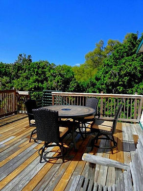 Large 2nd floor deck with table for six, view out over treetops with bright blue sky.