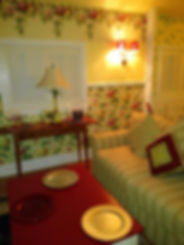 Cottage Sitting area with feather couch, red top coffee table and Ethan Allen pine table.