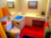 Grace's Charm bathroom with large retro blue sink and honey pine flooring.