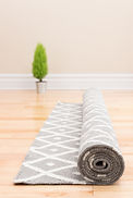 A roll of carpet being unrolled on a bare wood floor