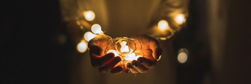 open hands with a chain of light, symbolizing giving help