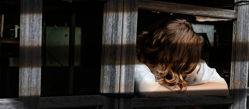 Person looking out of wooden window frame down and away from viewer