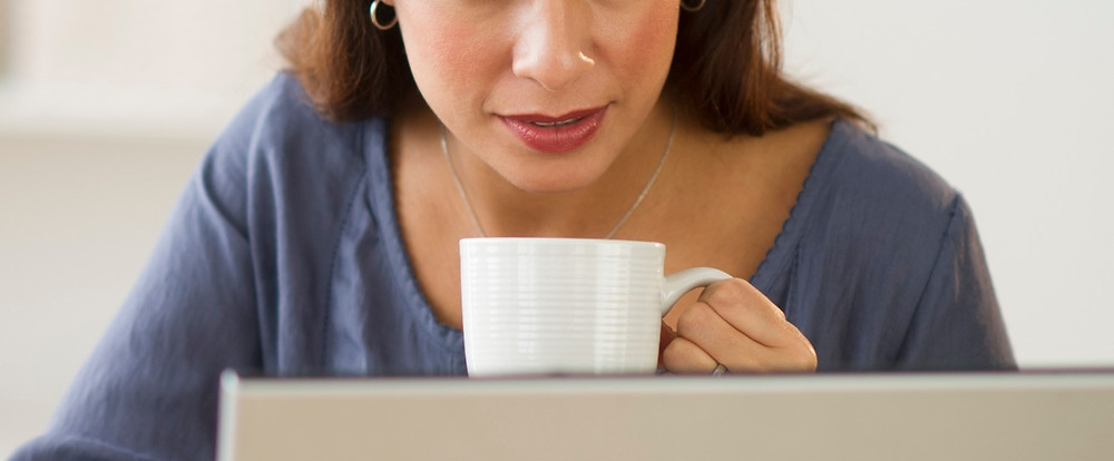 Woman with a cup in her hand in front of a laptop during video therapy