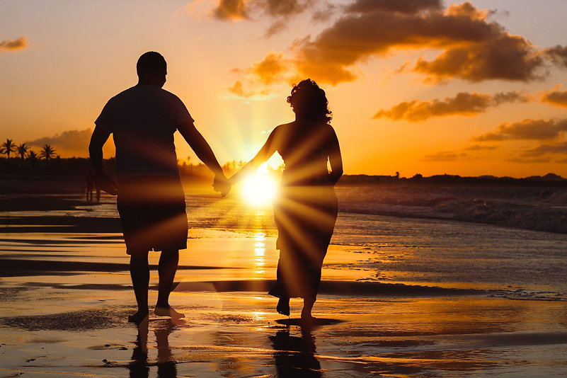 couple walking hand in hand on beach with sunset in the background