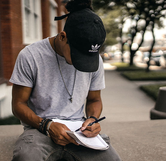 Black teen boy, deep in tought, writing in a note book
